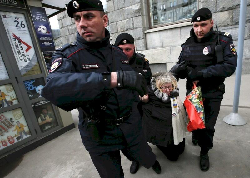 Rusya'da Putin karşıtı protestolar sırasında gözaltına alınan bir vatandaş.